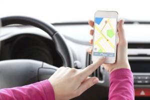 Frau im Auto mit Navi auf Smartphone